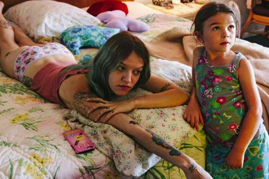 Mooney en robe à motifs les yeux levés vers la télé hors champ, et sa mère, cheveux turquoise et couverte de tatouages, étalée en petite culotte sur le lit.