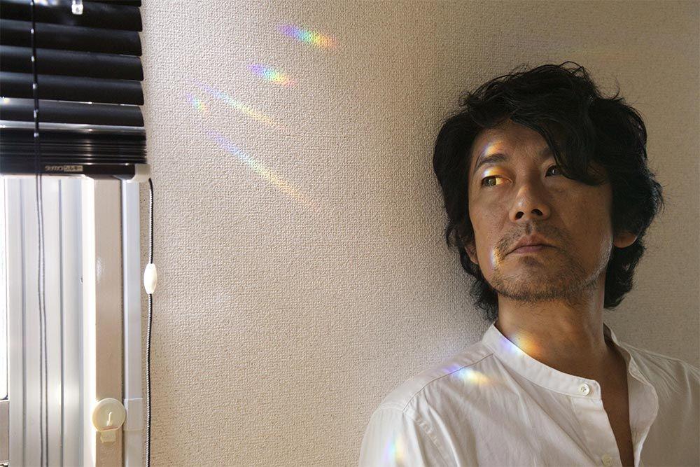 Le photographe dos au mur, à côté d'une fenêtre qui renvoie des fragments d'arc-en-ciels dans la pièce