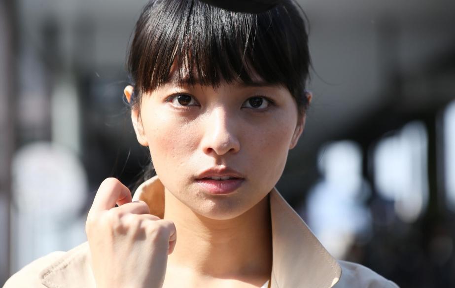 Gros plan sur le visage de la jeune femme audiodescriptrice, dehors, la main près du visage, dans un moment de suspension-interrogation