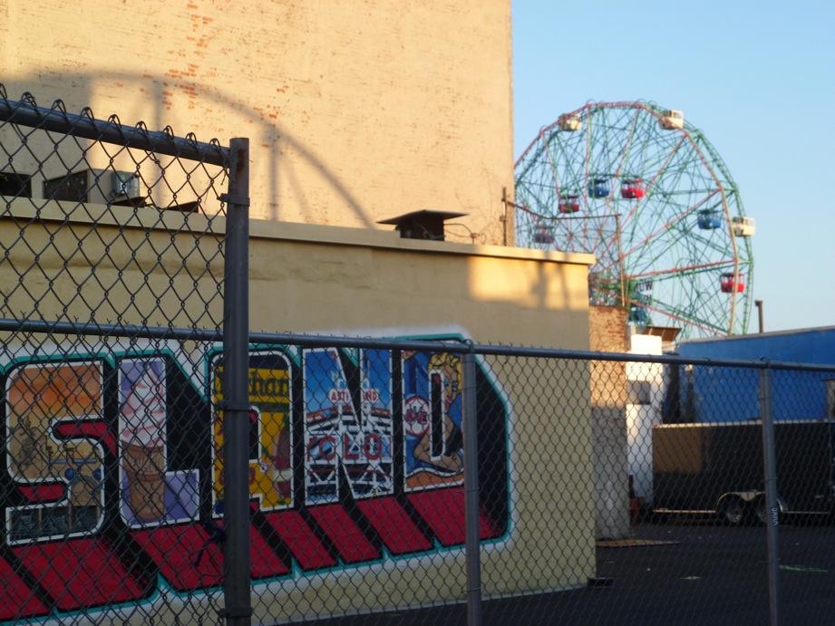 Bout d'une fresque 'Coney Island' avec grillages et un bout de la grande roue qui apparaît un peu floue derrière