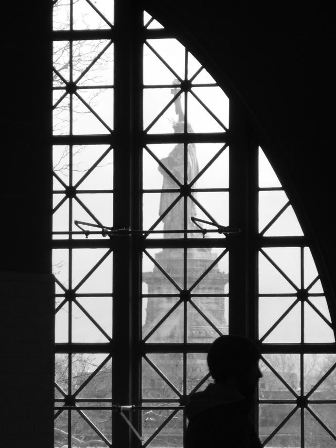 Statue de la Liberté visible derrière une fenêtre d'Ellis Island et silhouette en sens inverse à contre-jour