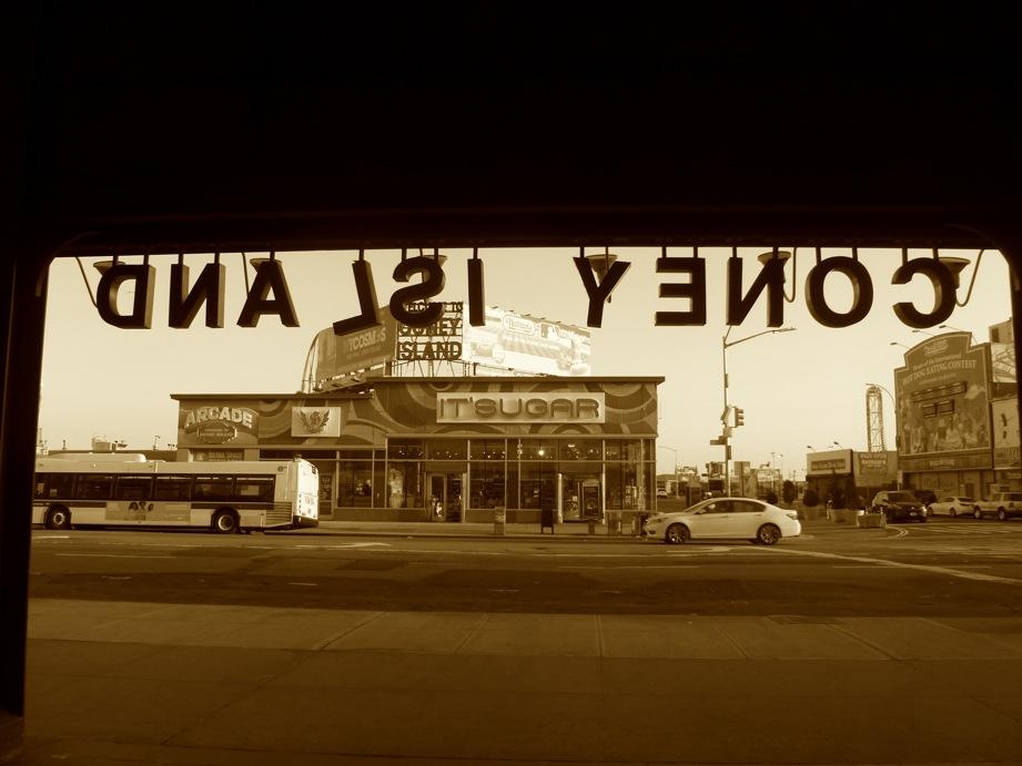 Nom de la station vu à l'envers, avec un magasin de bonbons derrière - en sépia