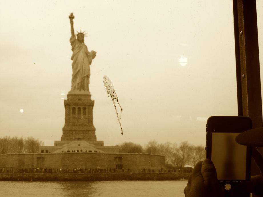 Statue de la Liberté au travers de la vitre du bateau, avec une chiure d'oiseau