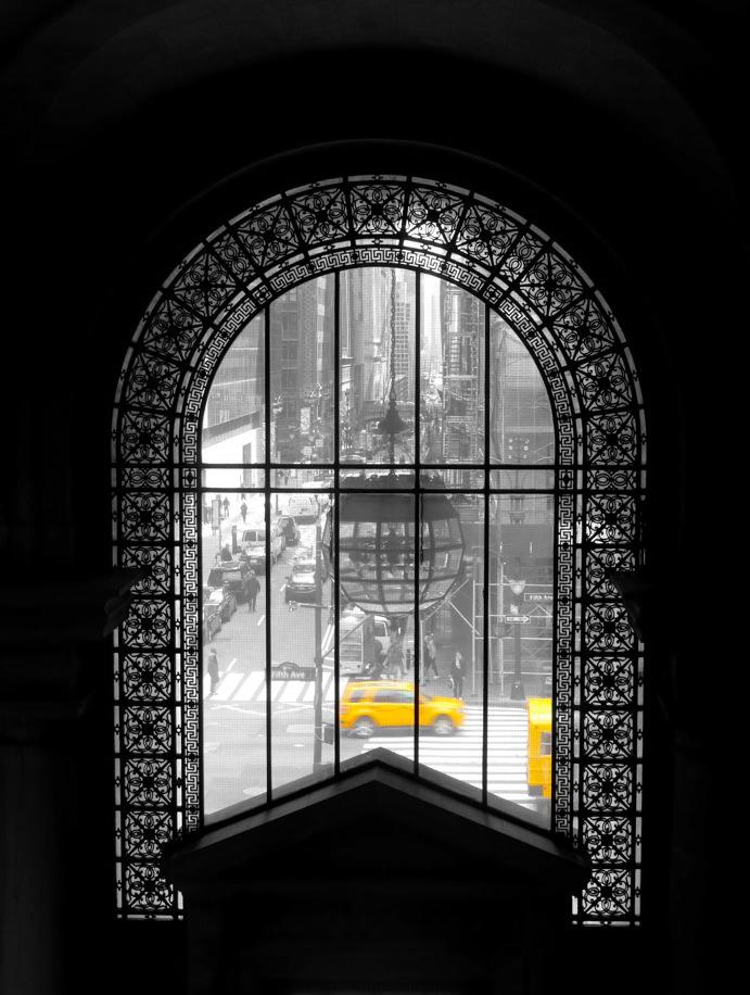 Taxi jaune visible à travers une fenêtre ornementée de la Public Library - reste de la photo en noir et blanc