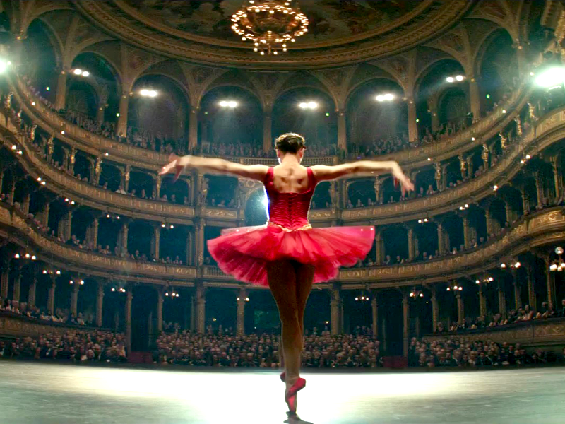 L'héroïne en tutu rouge sur scène, de dos, vue depuis l'arrière-scène