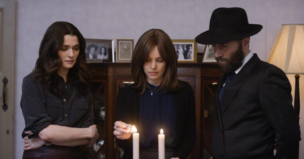 Ronit (bras croisés), son ex-amante Etsi (qui allume les cierges du shabbat) et le mari de cette dernière David (chapeau et barbe juive)
