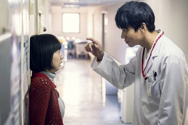 Médecin pointant l'index vers le doigt d'une jeune femme collée au mur