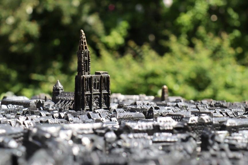 Plan miniature en 3D, d'où se détache la cathédrale, sur fond flou de verdure