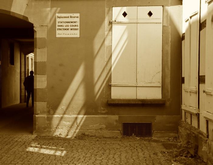 Lumière qui tombe oblique sur des volets à losange jusque sur les pavés d'une cour, une silhouette disparaissant par le passage adjaçant.