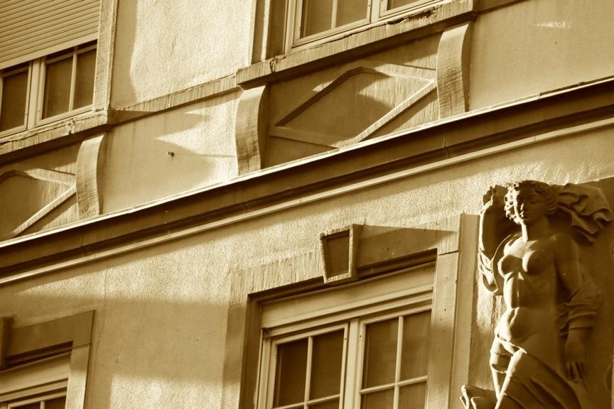 Lumière de la golden hour rasant une façade et les seins d'une statue