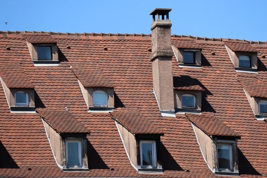 Toit avec plein de petites fenêtres et une cheminée (sans cigogne)