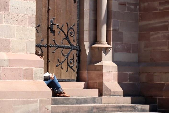 Fragments d'une lectrice derrière un pan de mur, sur les marches de l'église
