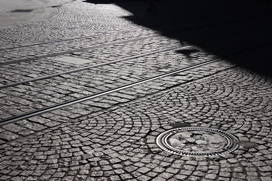 Pavés, lignes du tramway et plaque d'égout rasés par la lumière de la golden hour