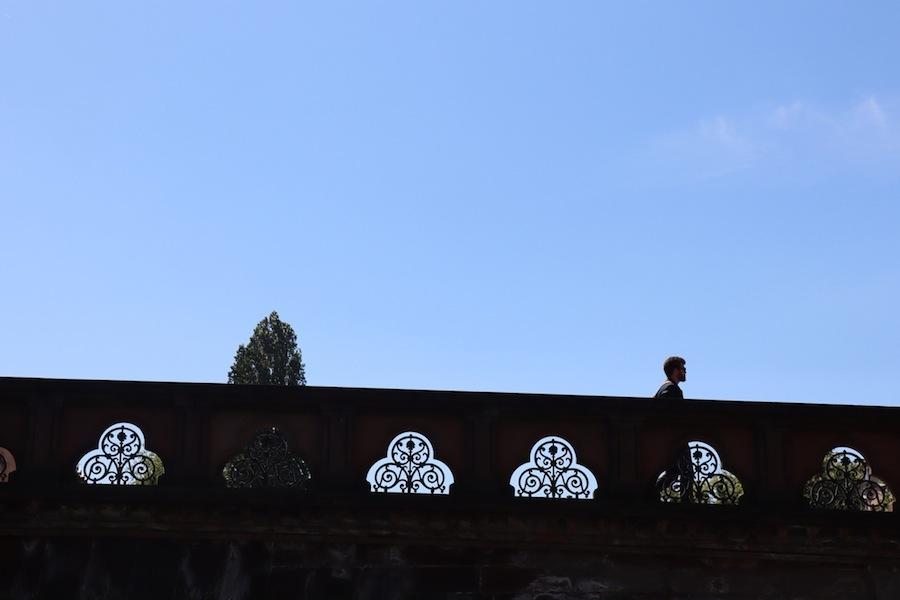 Pont vu d'en contrebas, avec des découpes en fer forgé, la cime d'un peuplier à gauche, un piéton à droite