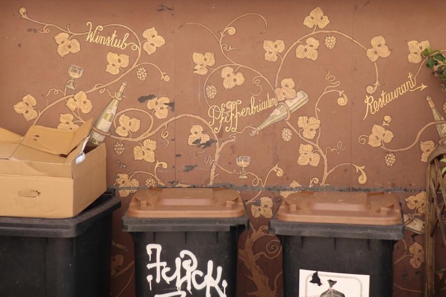 Mur décoré de vignes et de bouteilles… sous lequel sont entreposées les poubelles