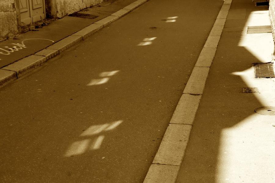 Quatre reflets de fenêtres égrainés sur la chaussée