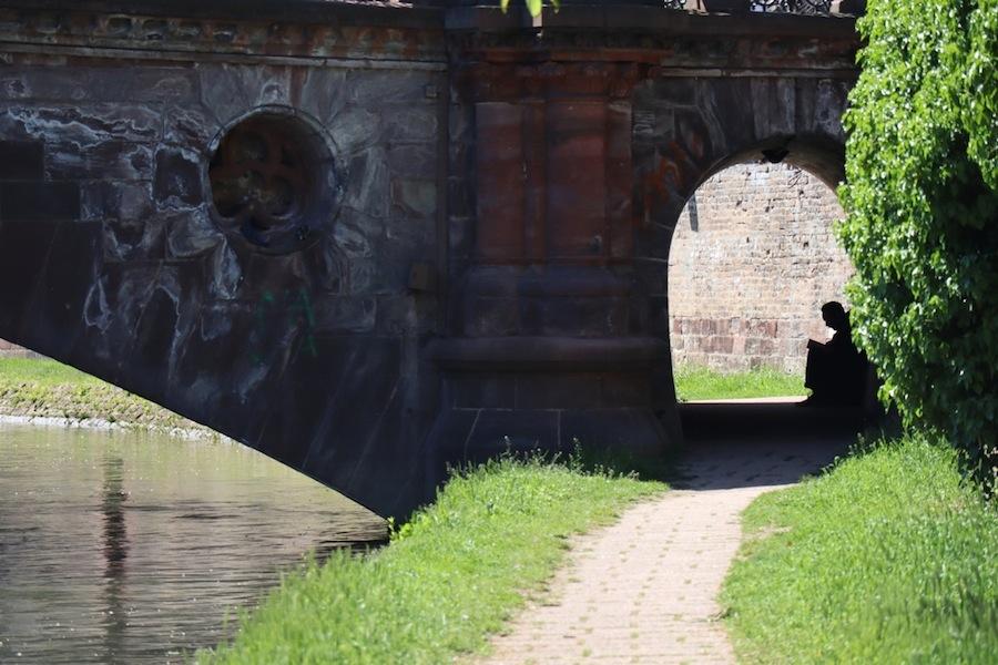 Silhouette en train de lire sous le passage d'un pont fluvial
