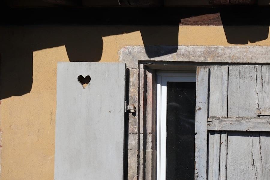 L'ombre des colombages mord sur un volet troué d'un coeur