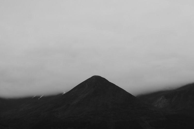 Téton de montagne juste devant la brume qui fait tout disparaître derrière lui, qui trouve ainsi un fond contre lequel se découper