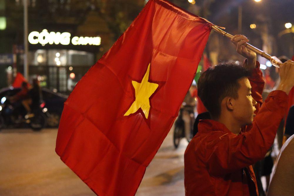Drapeau vietnamien porté par un supporter de foot après un match gagné